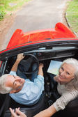 Mature couple in red convertible looking at camera — Stock Photo