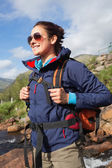 Brunette wearing rain jacket and sunglasses smiling — Stock Photo