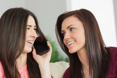 Two happy girls calling someone with a mobile phone — Stock Photo