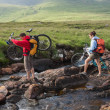 Couple crossing a river holding their bikes — Stock Photo