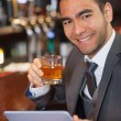 Cheerful businessman working on his tablet while having a whiskey — Stock Photo #31470467