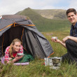 Smiling couple cooking outdoors on camping trip — Stock Photo