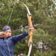 Stock Photo: Concentrating brunette practicing archery