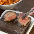 Stock Photo: Steak sizzling on hot stone plate being sliced