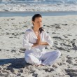 Peaceful woman practicing yoga against the sea — Stockfoto