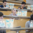 Focused students in lecture hall working on their futuristic tablet — Stock Photo