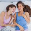 Girls wearing pajamas lying in bed and laughing — Stockfoto