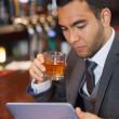 Serious businessman working on his tablet computer while having a whisky — Stock Photo