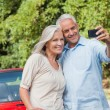 Cheerful mature couple taking pictures of themselves — Stock Photo