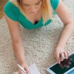 Kobieta, leżąc na podłodze jej odrabiania za pomocą tabletu — Zdjęcie stockowe