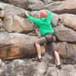 Determined man scaling a huge rock face — Stock Photo