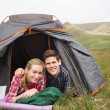 Happy couple lying in their tent and looking at camera — Stock Photo