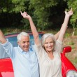 Cheerful mature couple posing by their red convertible — Stock Photo #31473481