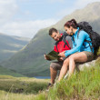 Couple taking a break after hiking uphill and reading map — Stock Photo