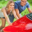 Smiling couple pushing their broken down car — Stock Photo