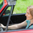 Smiling woman driving red cabriolet — Stock Photo