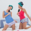 Girls in hair rollers singing with hairbrush — Stock Photo