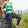 Attractive female rock climber leaning on rock face — Stock Photo #31474037