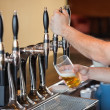 Barman pulling a pint of beer — Stock Photo