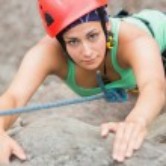 Focused girl climbing rock face — Stock Photo