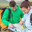 Stock Photo: Couple sitting after hiking uphill and consulting map