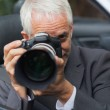 Mature paparazzi taking picture with professional camera — Stock Photo #31474331