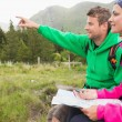 Couple sitting on a rock during hike using map and compass — Stock Photo