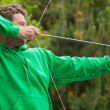 Man in green jumper about to shoot arrow  — Stock Photo