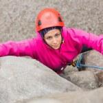 Smiling girl climbing up rock face — Stock Photo