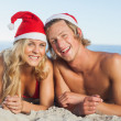 Couple lying on beach wearing christmas hats — Stock Photo #31475083
