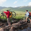 Couple crossing a stream holding their bikes — Stock Photo