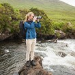 Blonde woman standing on a rock in a stream taking a photo — Stock Photo