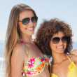 Two friends wearing sunglasses on the beach and smiling — Stock Photo #31475467