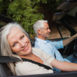 Side view of happy mature couple driving red cabriolet — Stock Photo