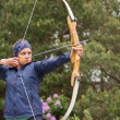 Stock Photo: Focused brunette practicing archery