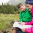 Couple sitting on a rock resting during hike using map and compass — Stock Photo