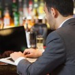 Handsome businessman working on his laptop while having a drink — Stock Photo
