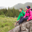 Couple sitting on a rock admiring the scenery — Stock Photo