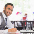 Smiling businessman writing while looking at camera — Stock Photo
