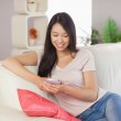 Pretty asian girl using her smartphone on the couch — Stock Photo #31476915