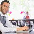 Smiling businessman working on laptop — Stock Photo