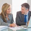 Two happy business people smiling to each other trying to understand figures — Stock Photo