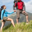 Stock Photo: Handsome hiker helping his girlfriend uphill