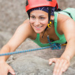 Happy girl climbing rock face — Stockfoto #31477435