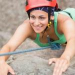 Happy girl climbing rock face — Stock Photo