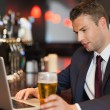 Businessman having a drink while working on his laptop — Stock Photo
