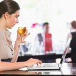 Attractive businesswoman holding wine glass while working on laptop — Stock Photo #31478133