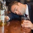 Stock Photo: Drunk businessmholding whiskey glass lying on counter