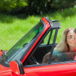Pretty blonde kissing her boyfriend in red cabriolet — Stock Photo