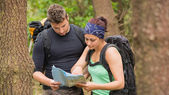Fit couple reading map in a forest — Stock Photo